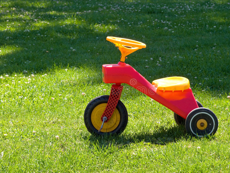 Tricycle on the grass. Bright colorful Tricycle standing on the grass stock photo