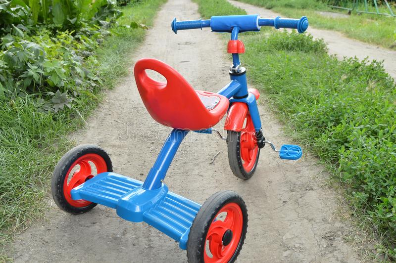 Tricycle kids bike Bicycle blue and red new is on the road in the garden to entertain children.  royalty free stock photo