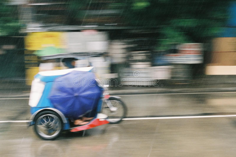 Tricycle in motion, on a rainy day. A panning shot of tricycle in motion, on a rainy day. photos taken in Philippines, asia royalty free stock photography
