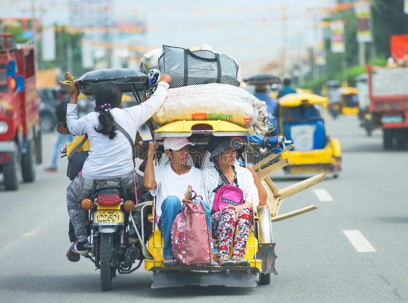 Tricycle travel in The Philippines. Koronadal City, The Philippines - August 6, 2015: Throughout The Philippines, the tricycle is a popular way of transportation stock images