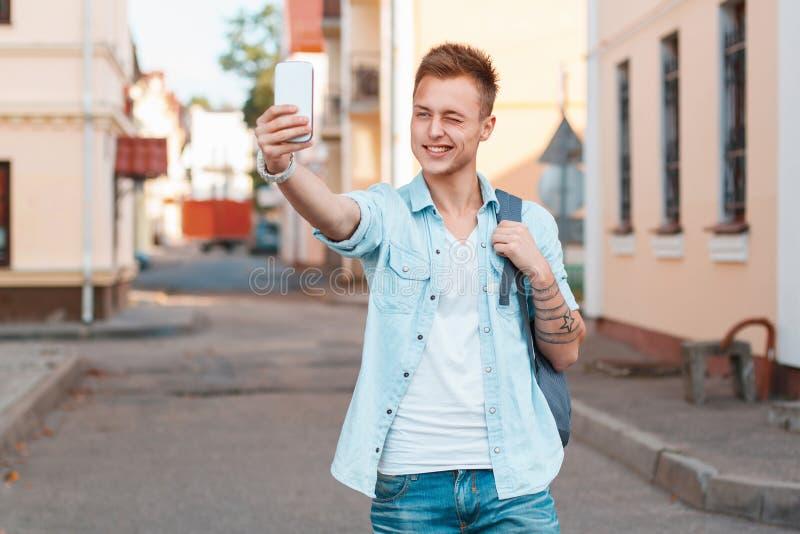 Trieb des jungen Mannes selbst auf dem Telefon und den Winks lizenzfreie stockfotografie