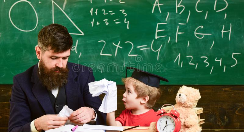 Tries and mistakes concept. Teacher with beard, father teaches little son in classroom, chalkboard on background. Boy stock photos