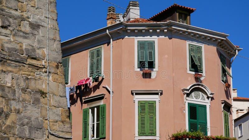 Trieste, Italia Fachada de una casa vieja con los obturadores verdes contra el contexto de la pared de piedra de la fortaleza imagenes de archivo