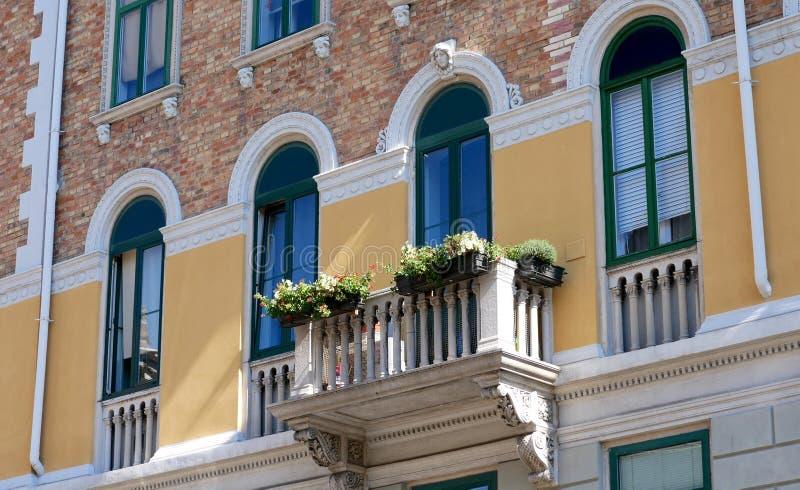 Trieste, Italia La fachada de una casa vieja Flores en el balcón imágenes de archivo libres de regalías