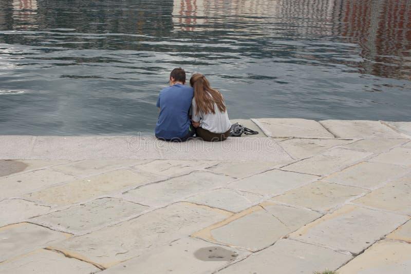 Trieste, o 5 de setembro de 2017, Itália: pares caucasianos novos que sentam-se em um cais de pedra que olha a água fotos de stock