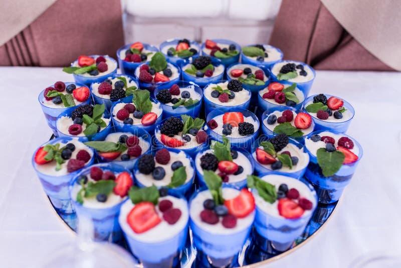 trifle Mycket förspiller tiden eller kakan i blåa exponeringsglas som dekoreras med bär Festlig i lager efterrätt i exponeringsgl royaltyfria bilder