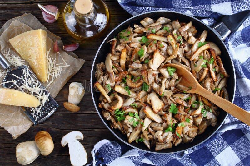 Trifolati de Funghi o porcini frito asperjado con perejil en sartén con la toalla de cocina en la tabla de madera oscura vieja imagen de archivo libre de regalías