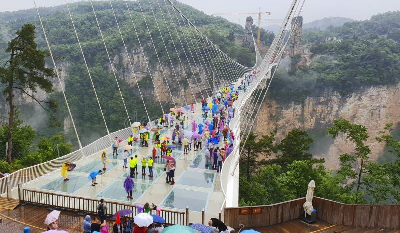 trigésimo mayo: Turistas que caminan y que toman imágenes en un día lluvioso en el puente de cristal Grand Canyon, Wulingyuan, Zh fotos de archivo