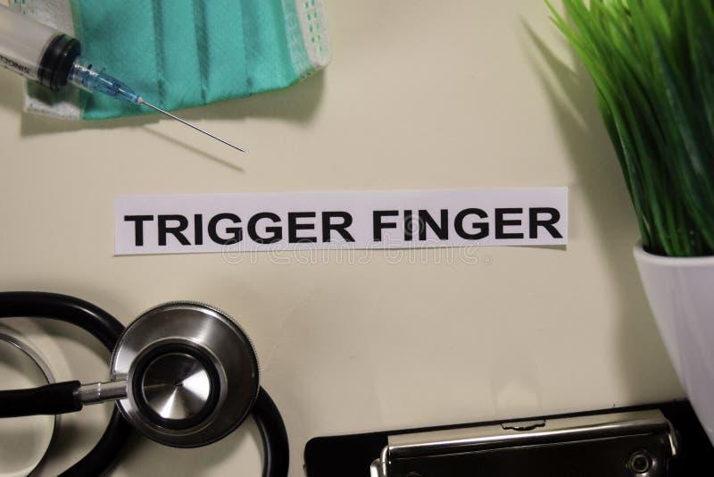 Triggerfinger mit Inspiration und Gesundheitswesen/medizinischem Konzept auf Schreibtischhintergrund stockfotografie