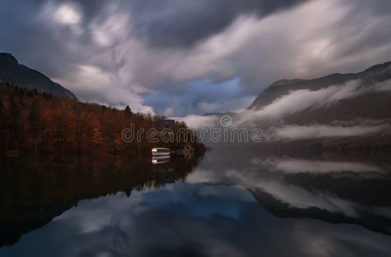 Triglav nationalpark, Slovenien, den största Bohinj-sjön Bohinjsko Jezero eller Wocheiner See Ovanliga moln i form av gångjärn arkivbild