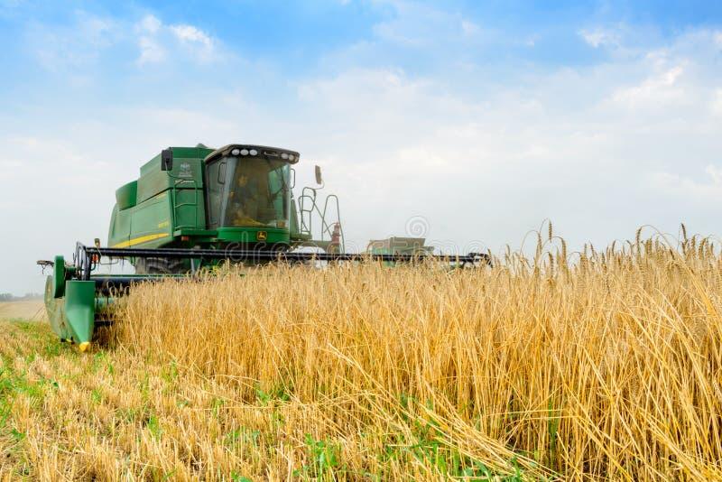 Trigo de John Deere Combine Harvester Harvesting en el campo imagen de archivo libre de regalías