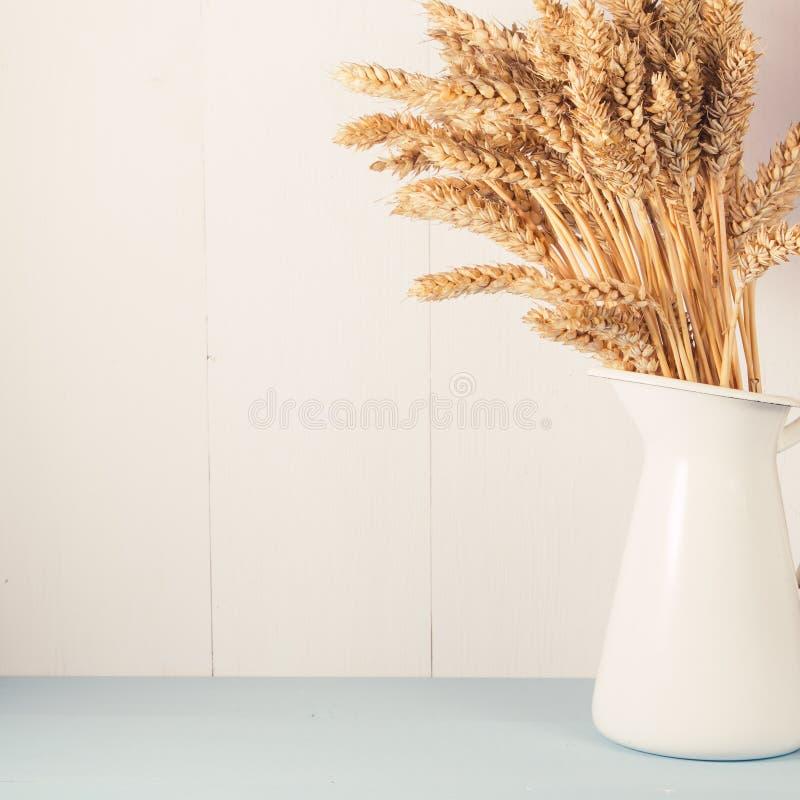 Trigo maduro en el florero blanco en fondo de madera imagenes de archivo