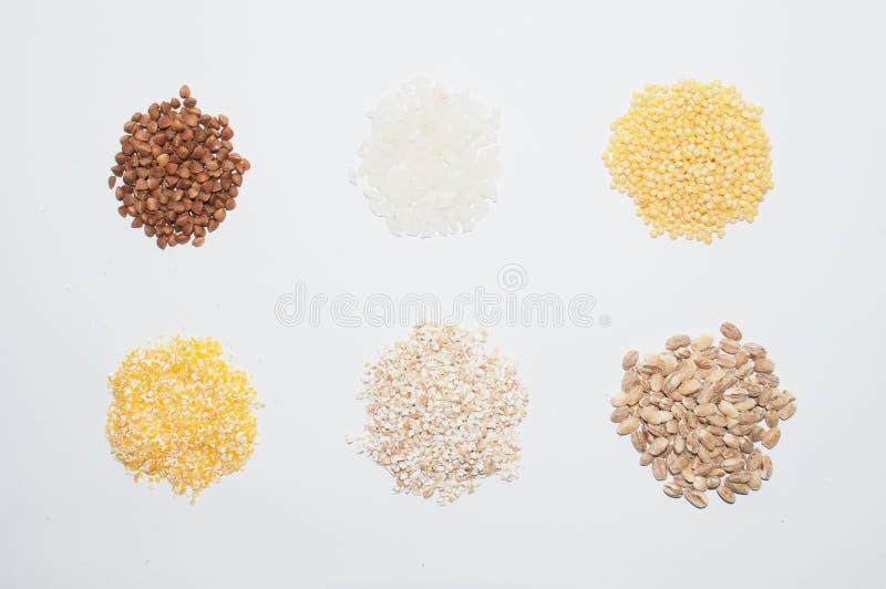 Trigo mourisco, arroz, painço, milho e cevada do papa de aveia em um fundo branco, visto da parte superior Dieta e comer saud?vel foto de stock royalty free