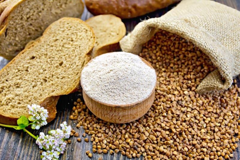 Trigo mourisco da farinha na bacia com grões a bordo imagens de stock royalty free