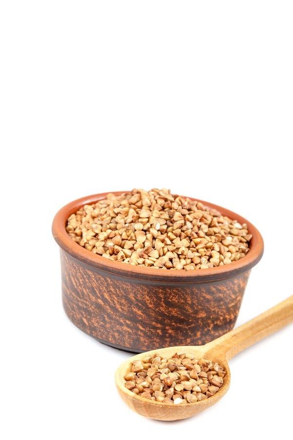 Trigo mourisco em uma bacia cerâmica e em uma colher de madeira fotografia de stock royalty free