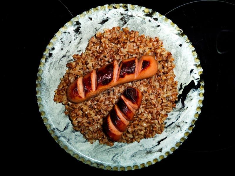 Trigo mourisco fervido com salsichas fritadas imagem de stock royalty free