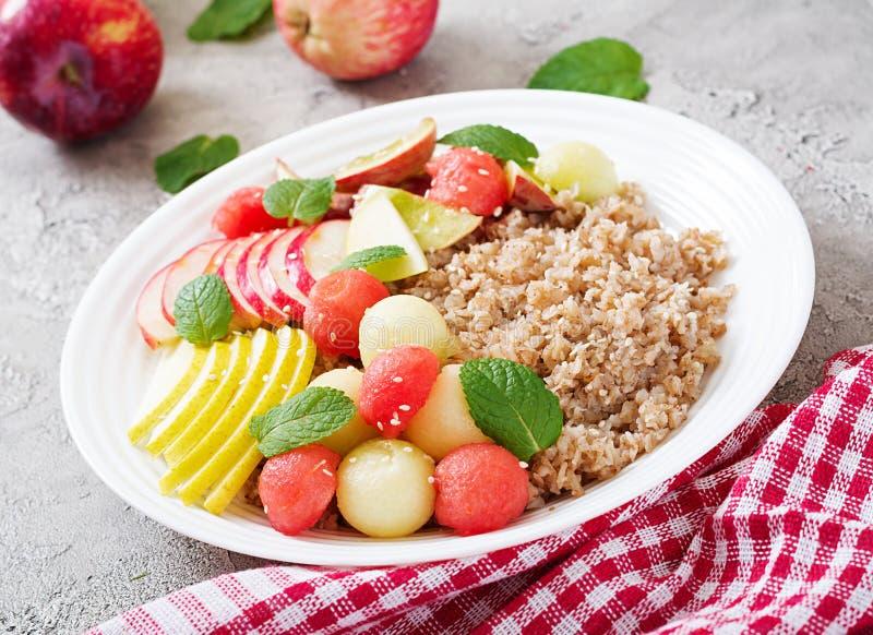 Trigo mourisco ou papa de aveia com melão, a melancia, a maçã e a pera frescos imagens de stock