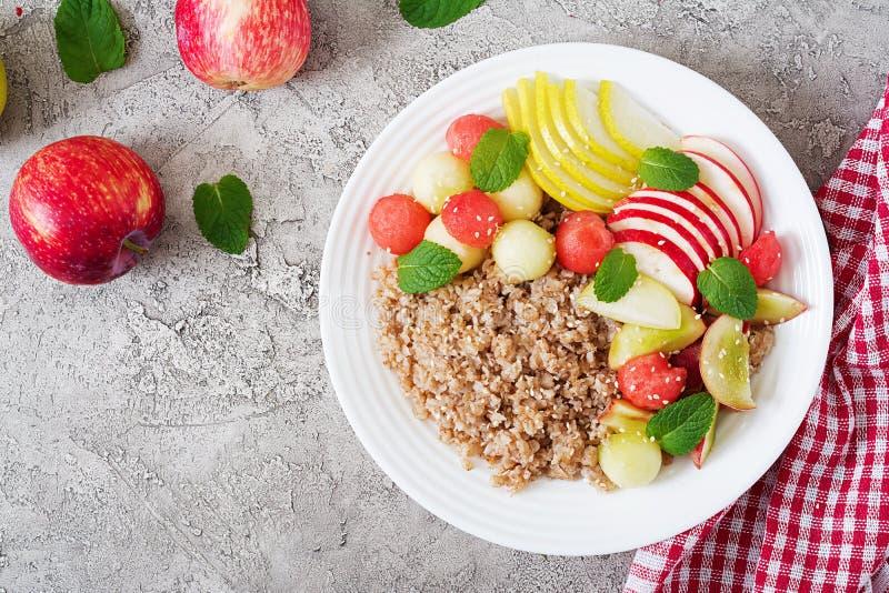 Trigo mourisco ou papa de aveia com melão, a melancia, a maçã e a pera frescos fotos de stock