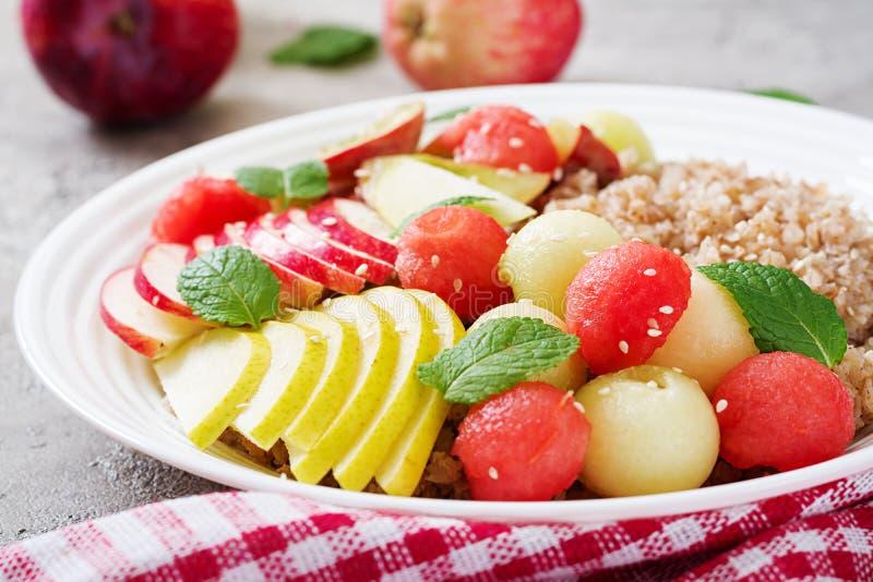 Trigo mourisco ou papa de aveia com melão, a melancia, a maçã e a pera frescos imagens de stock royalty free