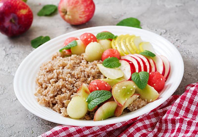Trigo mourisco ou papa de aveia com melão, a melancia, a maçã e a pera frescos fotografia de stock royalty free