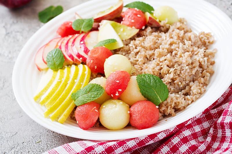 Trigo mourisco ou papa de aveia com melão, a melancia, a maçã e a pera frescos foto de stock
