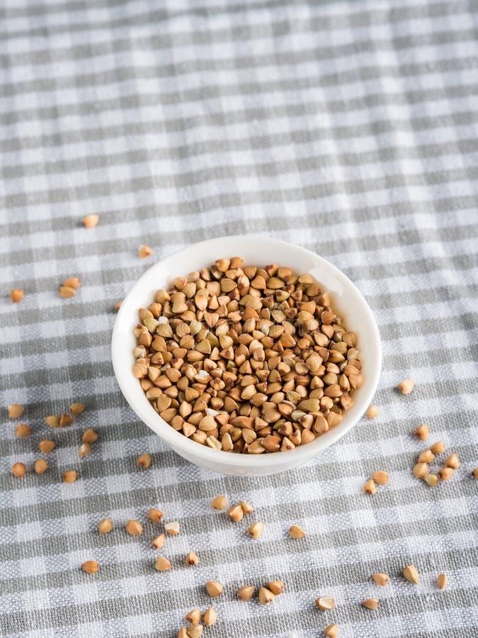 Trigo mourisco sem glúten da grão na bacia na mesa de cozinha imagem de stock royalty free