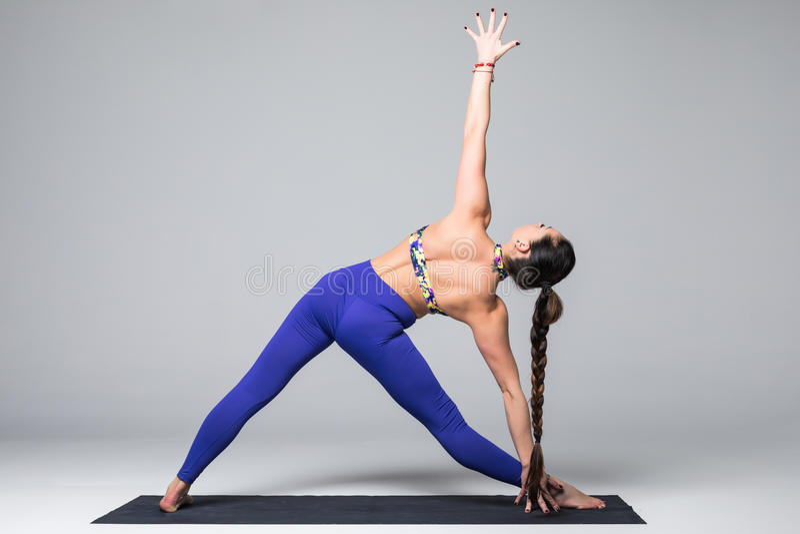 Trikonasana. Beautiful yoga woman practice yoga poses. On grey background. Yoga concept royalty free stock photography