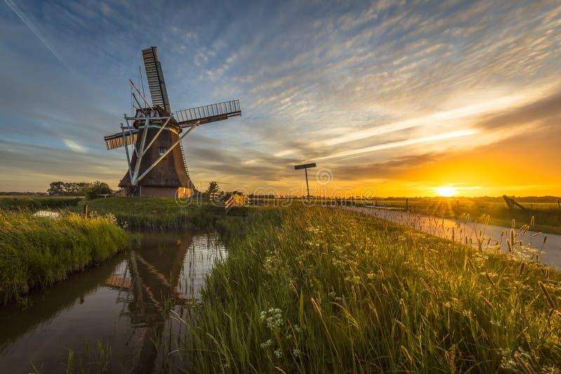 Trilha de ciclismo de madeira do canal do moinho de vento no por do sol fotografia de stock royalty free