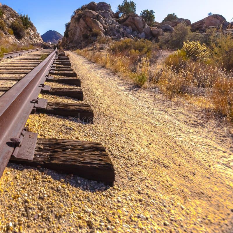 Trilha de estrada de ferro em um deserto seco e rochoso imagens de stock royalty free