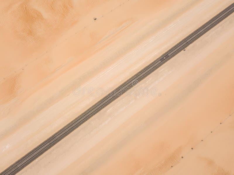 Trilha de estrada de ferro reta que passa através de um deserto arenoso foto de stock