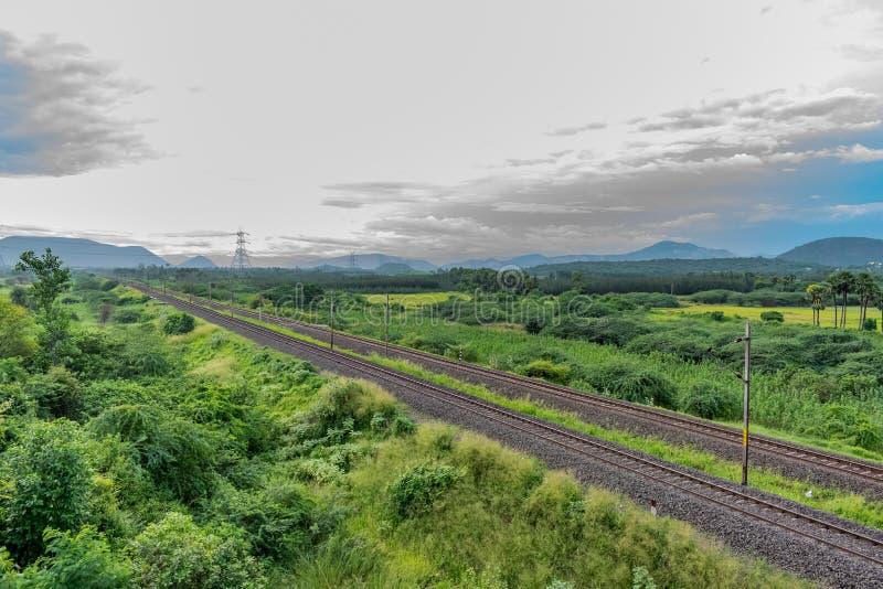 A trilha de estrada de ferro reta vai ao horizonte na paisagem verde sob o céu azul com nuvens imagens de stock royalty free