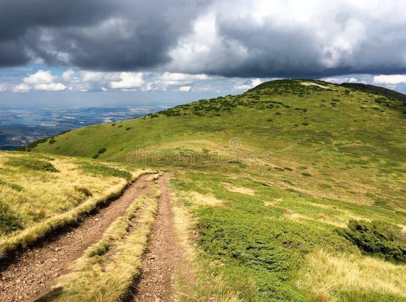 Trilha do cascalho através das montanhas com nuvens dramáticas fotos de stock royalty free