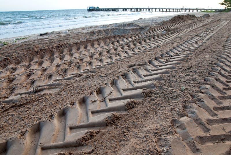 Trilha do pneu na praia da areia imagem de stock