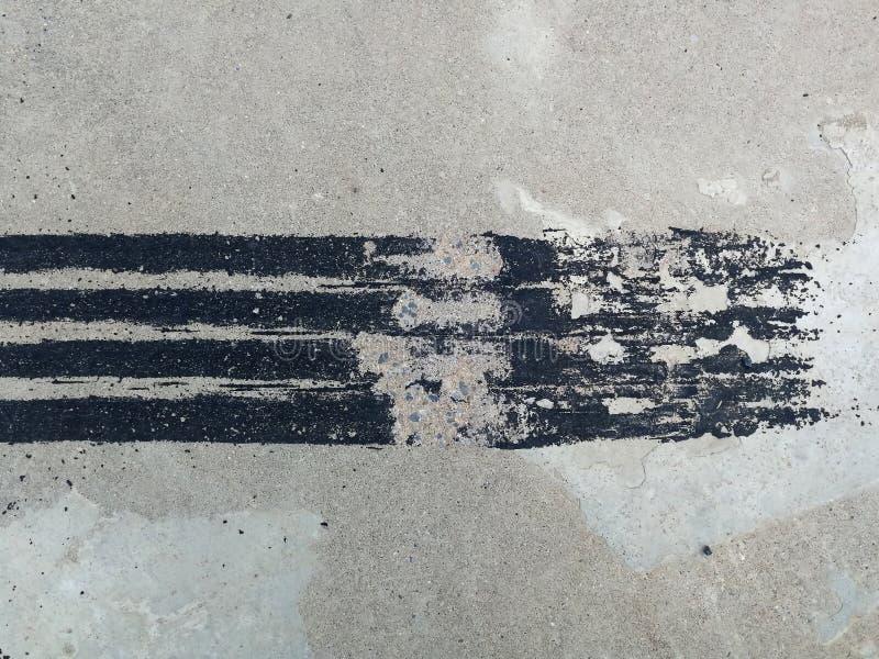 Trilha preta do pneu no concreto sujo após o freio repentino imagem de stock