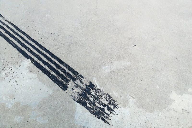 Trilha preta do pneu no concreto sujo após o freio repentino fotos de stock royalty free