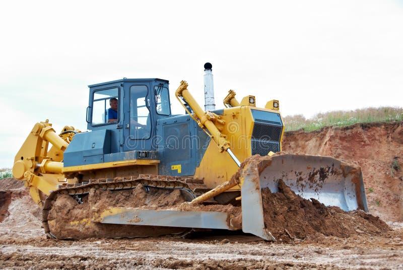 Trilha-tipo máquina escavadora da escavadora do carregador no trabalho foto de stock