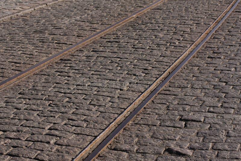 Trilhas de aço do bonde em uma rua de pedrinha velha imagens de stock royalty free