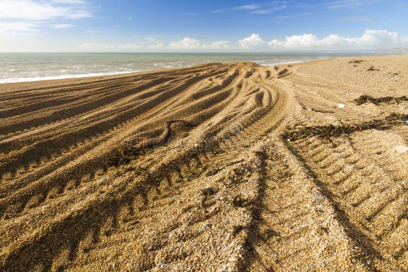 Trilhas de Caterpillar do escavador na praia rochoso fotos de stock royalty free