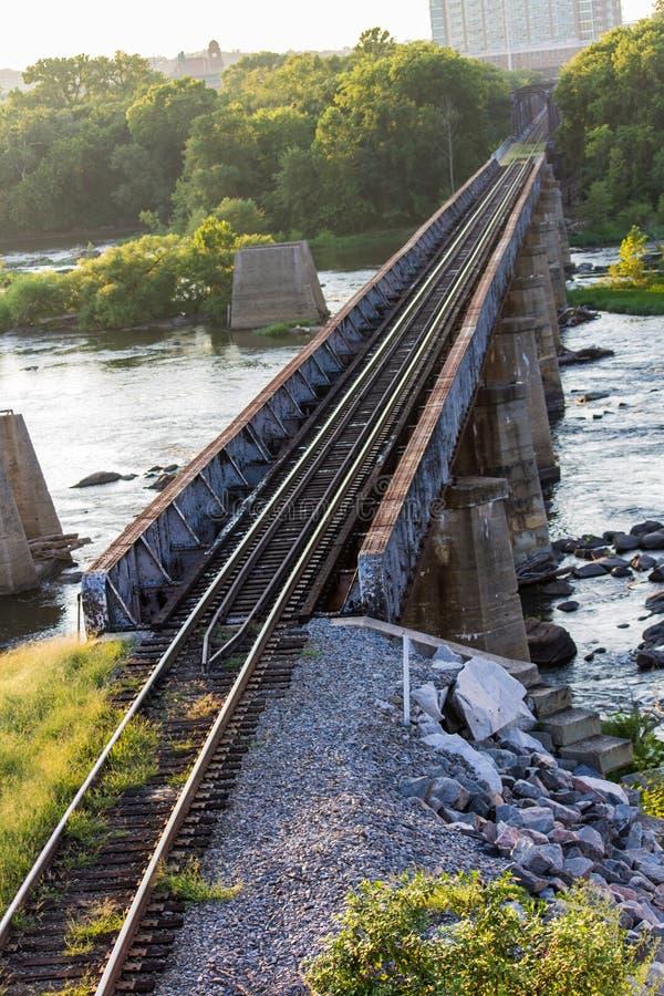 Trilhas de estrada de ferro sobre um rio raging imagem de stock