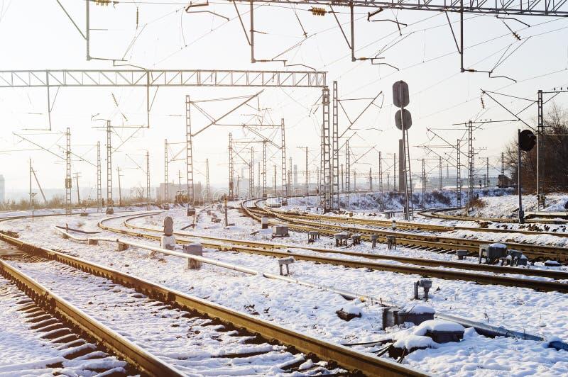 Trilhas de estrada de ferro na neve Vagões de estrada de ferro da mercadoria, inverno Fios de alta tensão acima das trilhas de es foto de stock royalty free