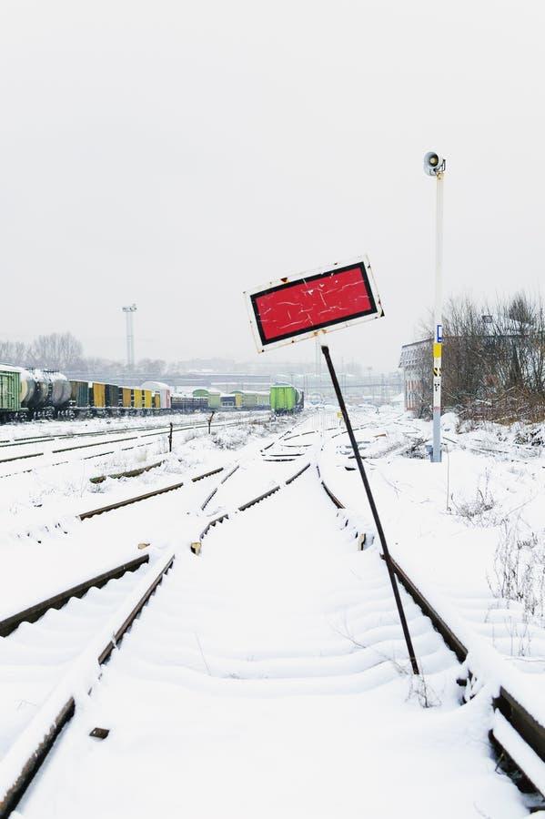 Trilhas de estrada de ferro na neve Vagões de estrada de ferro da mercadoria, inverno Fotografia vertical imagens de stock royalty free