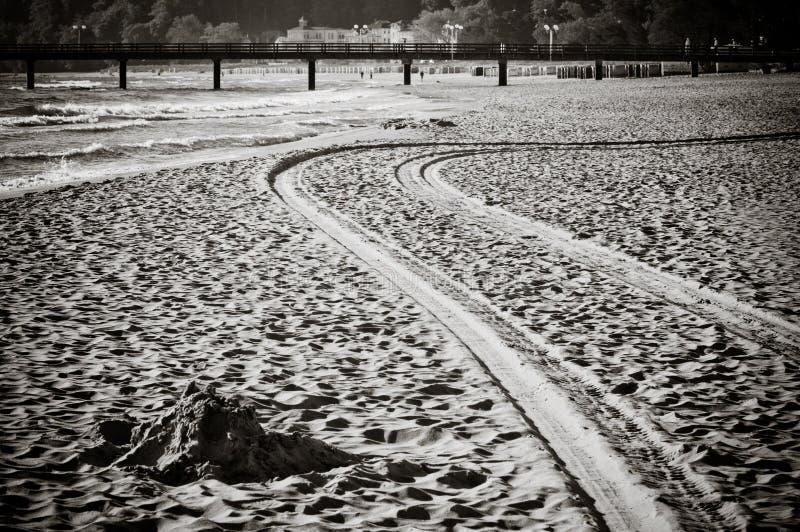 Trilhas de madeira do cais e do pneumático na areia na praia imagem de stock