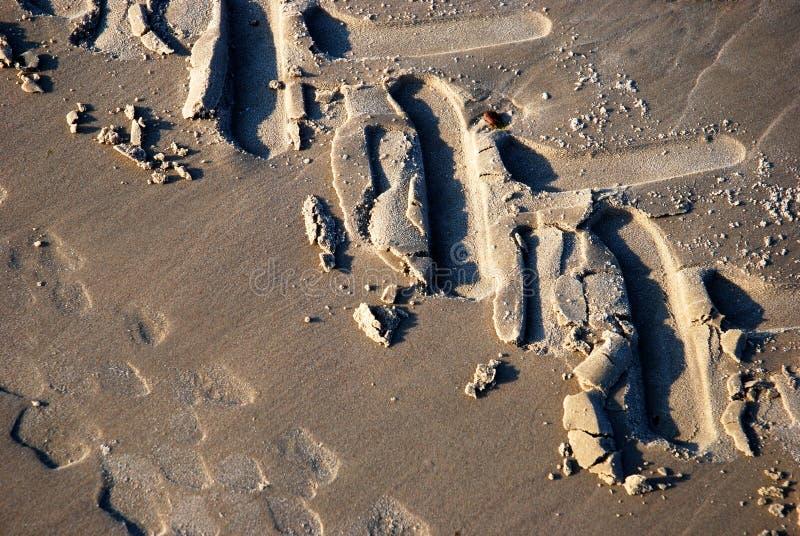 Trilhas detalhadas do pneu em uma praia imagens de stock