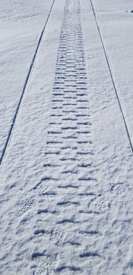 Trilhas do carro de neve na neve foto de stock