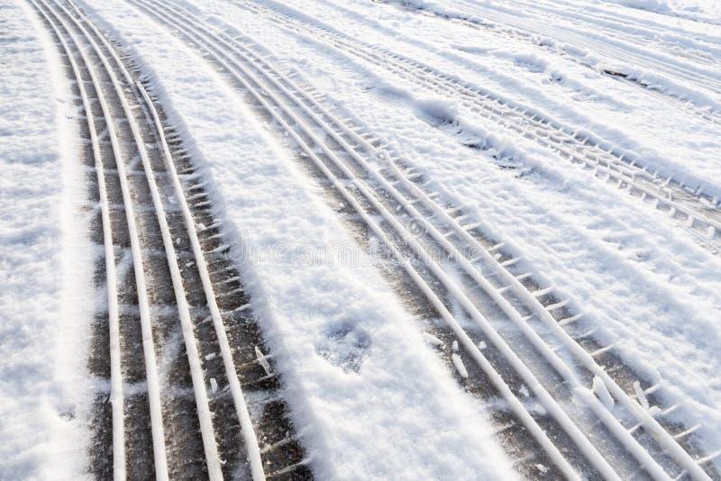 Trilhas do pneu de carro na neve na rua imagem de stock