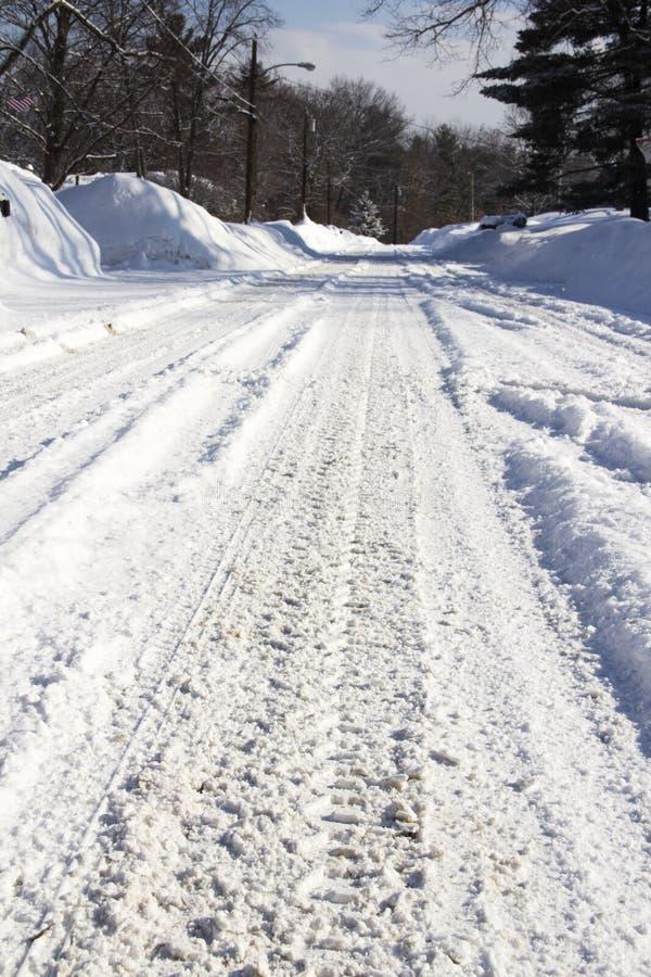 Trilhas do pneu em uma estrada coberto de neve fotografia de stock royalty free