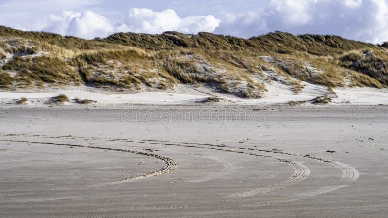 Trilhas do pneu na praia em Løkken, Dinamarca norte fotografia de stock