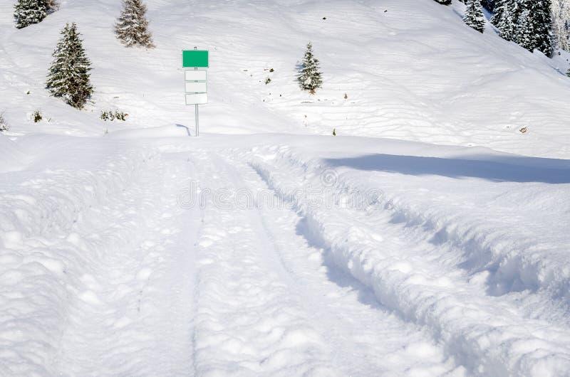 Trilhas em um campo coberto de neve imagens de stock