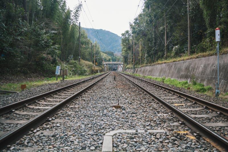 Trilhas japonesas do trem além de uma autoestrada imagens de stock