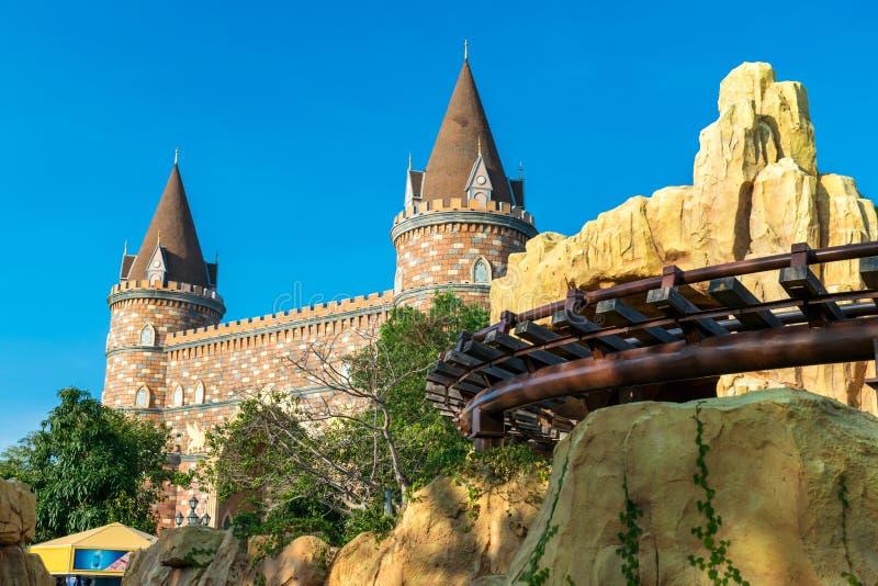 Trilhos e castelo feericamente no parque de diversões sob o sol de nivelamento foto de stock